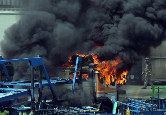쌍용차 사건 당시 노조원들이 바리케이트로 세워놓은 차량운반용 차에 불을 질러 연기가 피어오르고 있다. [중앙포토]