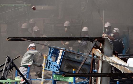 2009년 8월 4일 쌍용차 노조 평택공장 점거 농성 과정에서 사측이 포크레인과 지게차를 동원해 바리케이트를 치우는 작업을 시작하자 노조원들이 돌을 던지며 저항하는 모습. [중앙포토]