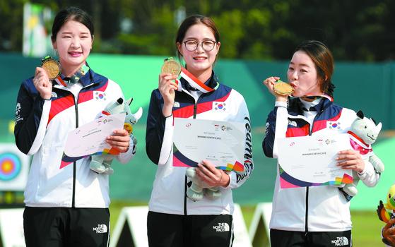 한국 여자양궁 대표팀 강채영·이은경·장혜진(왼쪽부터)이 금메달에 입을 맞추며 기뻐하고 있다. 한국 여자양궁은 아시안게임 단체전에서 6회 연속 금메달을 따내는 위업을 달성했다. [뉴시스]