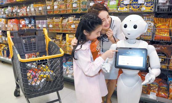 이마트는 4차 산업혁명 시대를 준비하기 위해 자율 주행 카트, 로봇 도우미를 시범운영한다. 성수점에서 로봇 도우미 '페퍼(Pepper)'가 카드 행사를 안내해주고 있다. [사진 이마트]
