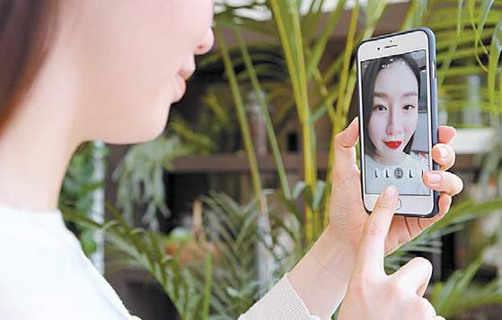 현대백화점이 첨단 기술을 활용한 리테일테크 실험에 속도를 내고 있다. 고객이 더현대닷컴 앱을 이용해 가상으로 립스틱을 발라보고 있다. [사진 현대백화점]