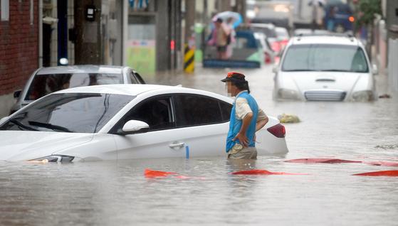지난 1일 광주광역시 남구 주월동 골목길이 폭우에 침수된 가운데 한 주민이 물에 잠겨버린 차량을 바라보고 있다. [뉴시스]