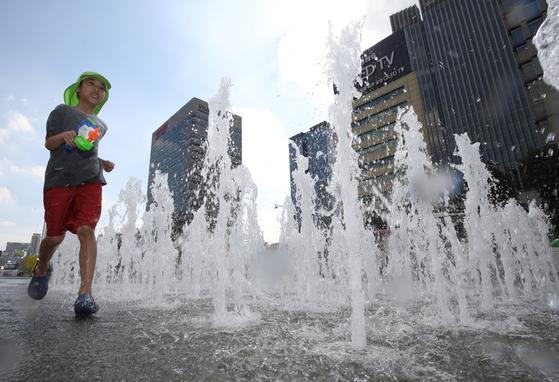 서울 종로구 광화문 광장을 찾은 어린이들이 바닥분수에서 물놀이를 즐기고 있다.[연합뉴스]