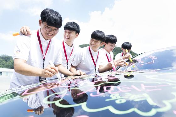 '2018 아우스빌둥' 출범식에 참가한 교육생들이 메르세데스-마이바흐 S클래스 차량에 자신의 다짐을 적고 있다. [사진 메르세데스-벤츠코리아]