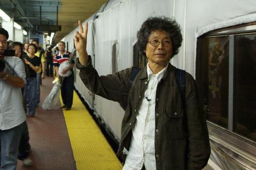 2005년 9월 미국 뉴욕 펜실베이나 역 승강장에서 흰 천으로 덮은 암트랙 기차에 출발 신호를 주던 설치미술가 고 전수천씨. 기차를 붓 삼고 미국 대륙을 캔버스 삼아 움직이는 드로잉을 그리는 그의 통 큰 프로젝트는 당시 미술계의 큰 화제였다. [중앙포토]