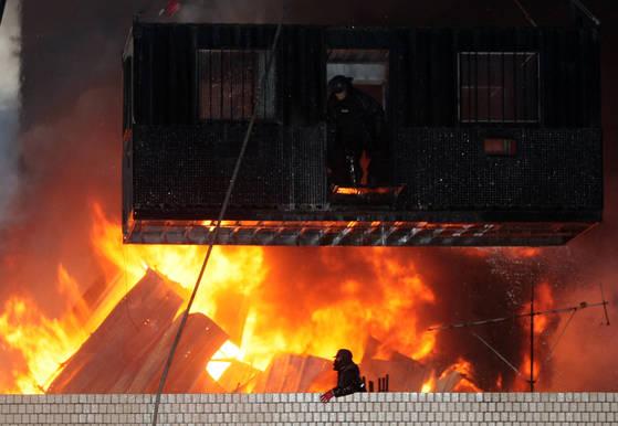 사진은 용산 참사가 발생한 2009년 1월 20일 서울 한강로 2가 재개발지역의 남일당 건물 옥상의 사고 현장. 경찰의 강제진압이 진행된 가운데 옥상에 설치한 망루에 불이 나 쓰러지고 있다. [연합뉴스]