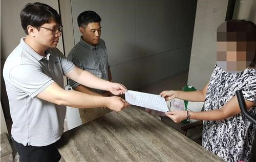 지난달 30일 오후 인천시 연수구 모 아파트단지에서 지하주차장 진입로를 자신의 캠리 승용차로 막아 물의를 빚은 50대 주민(오른쪽)이 입주자대표단에 사과문을 전달하고 있다. 해당 아파트단지 입주자대표단 제공