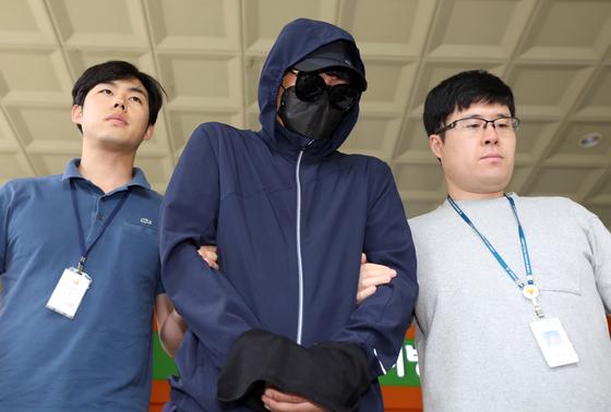 지난 7월 2일 양예원씨 등에게 노출 사진을 강요하고 성추행한 혐의를 받는 최모씨가 서울서부지법에서 영장실질심사를 마치고 차량으로 향하는 모습. [뉴스1]