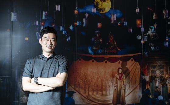 창작 뮤지컬 '웃는 남자' 공연 사진 앞에 선 오필영 무대디자이너. 지난 7월 서울 서초동 예술의전당에서 개막한 '웃는 남자'는 5일부터 한남동 블루스퀘어로 장소를 옮겨 공연을 이어간다. [권혁재 사진전문기자]