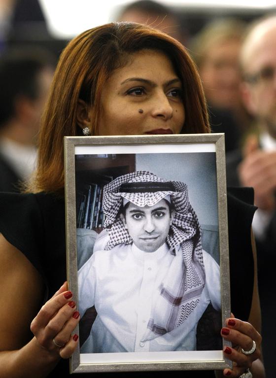 사우디아라비아 인권운동가 라이프 바다위의 사진을 들고 있는 아내 엔사프 하이다르. [AP=연합뉴스]
