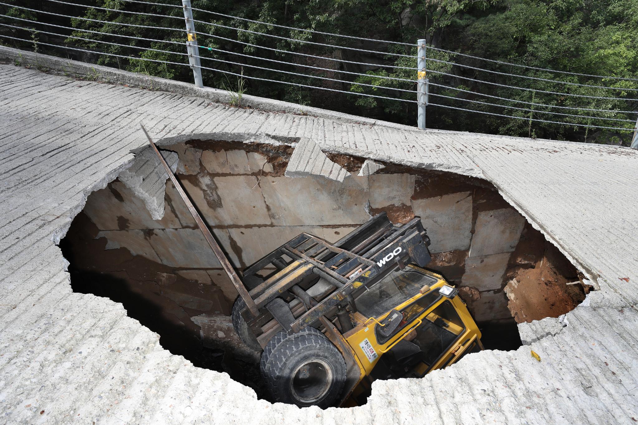 5일 경기도 의정부시 사패산 회룡사 입구에서 가로 세로 5m, 깊이 5m 크기의 땅꺼짐이 생겨 운행 중이던 지게차가 빠져 있다. [연합뉴스]