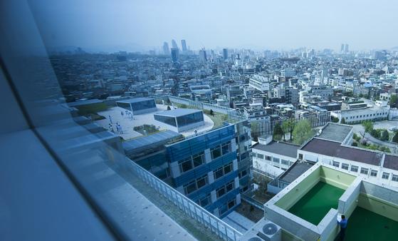 국립정신건강센터 병동의 창문에서 바라본 서울시내 전경. 센터 건물 옥상의 하늘정원에서 환자들이 의료진과 함께 산책을 하고 있다. 오른쪽 아래는 6·25 전쟁의 충격으로 정신질환을 얻은 환자들을 치료하기 위해 1962년 지은 옛 병동이다.(사진과 기사내용은 관련 없음)[중앙포토]