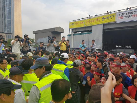 6일 오전 법원 노무인력이 구 노량진수산시장에 대한 강제집행을 하려 하자 붉은 조끼를 입은 구시장 상인들이 막아서고 있다. 조한대 기자