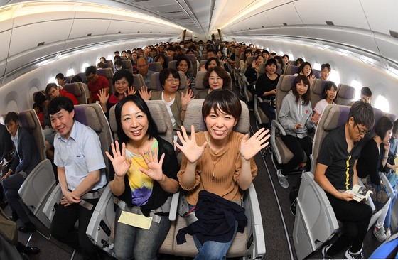 지난해 추석 연휴를 하루 앞둔 9월29일 인천에서 일본 오사카로 첫 운항하는 아시아나항공기 A350기 안에서 승객들이 손을 흔들고 있다. [아시아나항공]