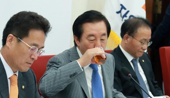 김성태 자유한국당 원내대표가 6일 서울 여의도 국회 본청에서 열린 대정부질문 의원 회의에서 목을 축이고 있다. [뉴스1]