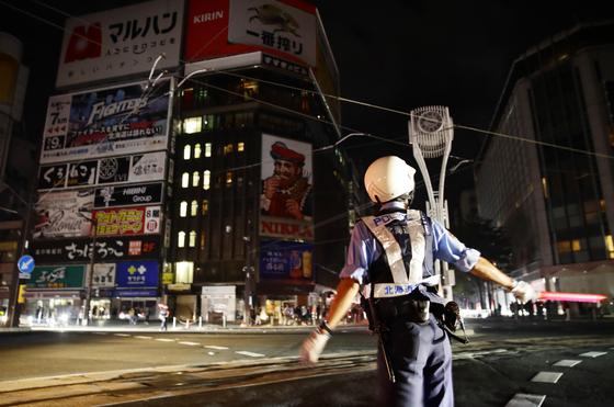 지진으로 정전이 발생한 삿포로 시내 교차로에서 교통정리를 하는 경찰. [교도=연합뉴스]