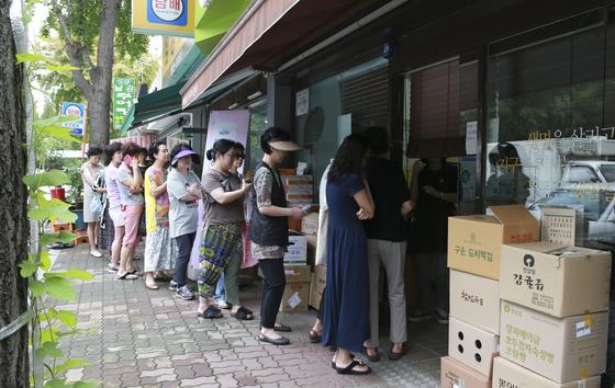 주부들이 서울 서초구 반포동에 있는 유기농 상품을 판매하는 매장 앞에서 문 열기를 기다리고 있다. 임현동 기자