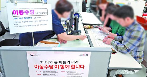 20일 서울 서대문구 남가좌1동 주민센터에서 한 부부가 오는 9월부터 아동 1명당 월 10만원씩 지급되는 아동수당을 신청하고 있다. [연합뉴스]