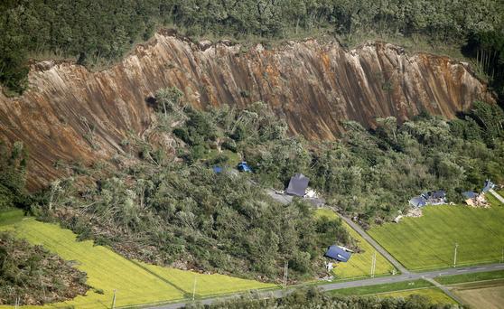 일본 홋카이도에 강진이 발생한 6일 오전 홋카이도 아쓰마 마을 가옥들이 산사태로 인한 흙더미에 파묻혀 있다. [교도=연합뉴스]