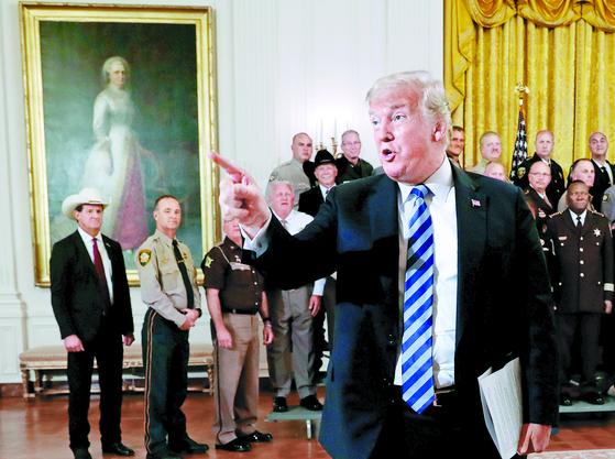 """지난 5일(현지시간) 도널드 트럼프 미국 대통령이 백악관에 전국 보안관을 초청한 자리에서 익명의 뉴욕타임스(NYT) 칼럼 기고자와 NYT를 싸잡아 비난했다. 그는 '(칼럼 기고자는) 망해 가는 NYT의 또 다른 거짓 취재원"""" '국가 안보를 위해 NYT는 기고자를 정부에 넘겨야 한다""""고 주장했다. [로이터=연합뉴스]"""