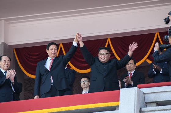 북한 김정은 국무위원장(오른쪽)이 리잔수 중국 전인대 위원장의 손을 치켜 올렸다. 9일 평양 김일성 광장에서 열린 북한 정권수립 70주년 기념 군사 퍼레이드 단상에서다. [AFP]