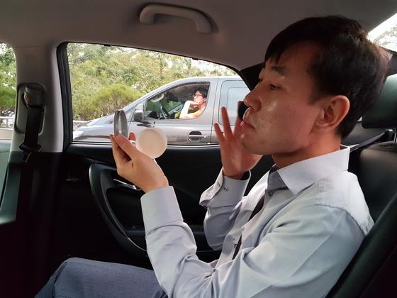 하태경 바른미래당 최고위원이 4일 오전 라디오 인터뷰를 하러가는 차 안에서 직접 화장을 하고 있다. 성지원 기자