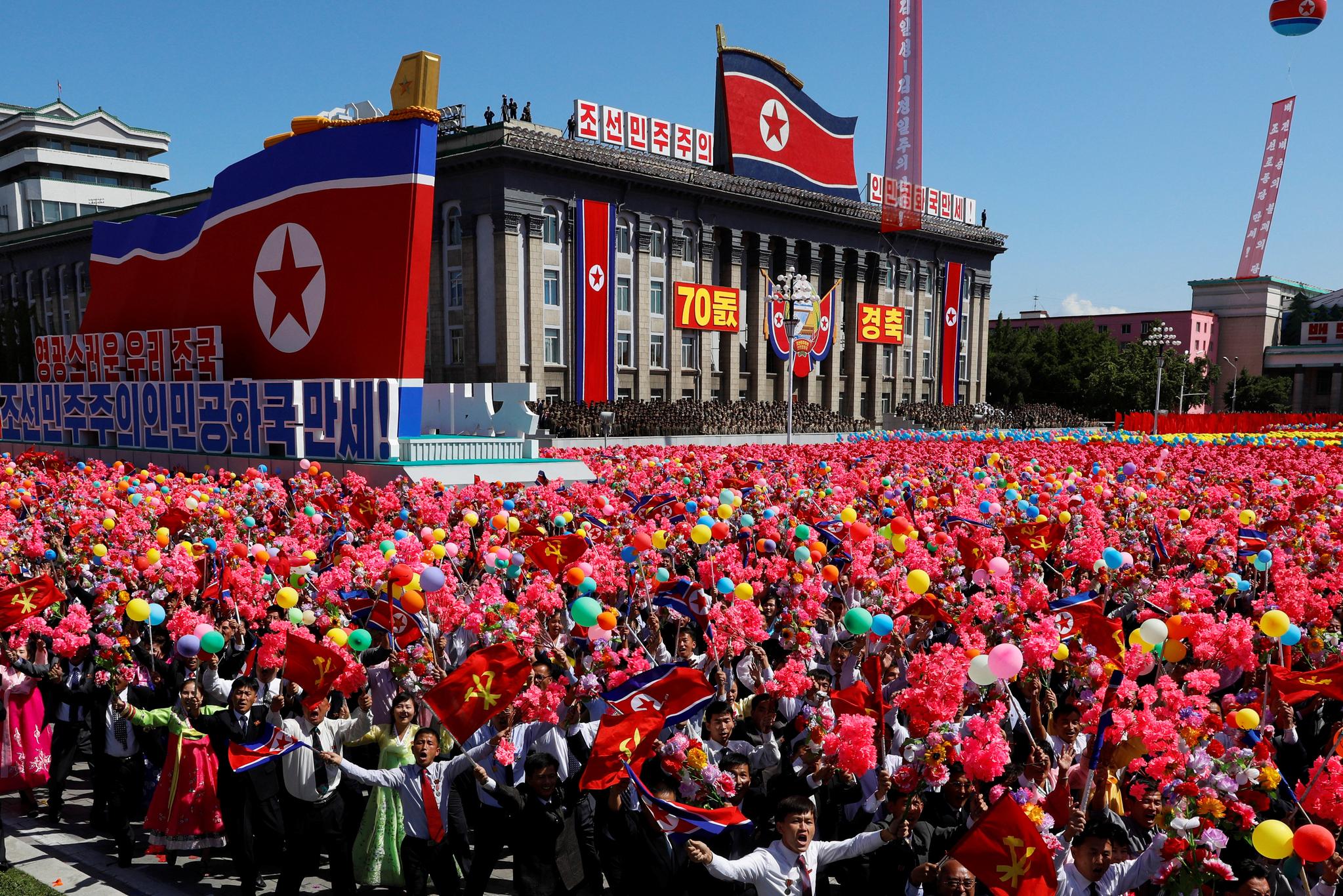 9일 북한 평양 김일성광장에서 열린 정권 수립(9.9절) 70주년 기념 열병식에서 주민들이 붉은 꽃과 형형색색의 풍선을 들고 행사에 참여하고 있다. 이날 열병식에서는 대륙간탄도미사일(ICBM)은 등장하지 않았다. [로이터=연합뉴스]