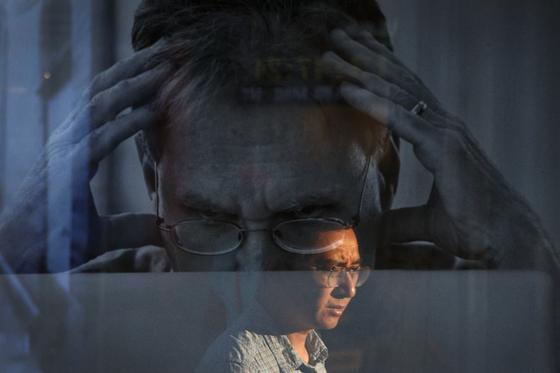 6일 중국 베이징의 한 쇼핑몰에 걸린 애플 맥북 광고 위로 한 남성의 모습이 반사됐다. AP=연합뉴스]