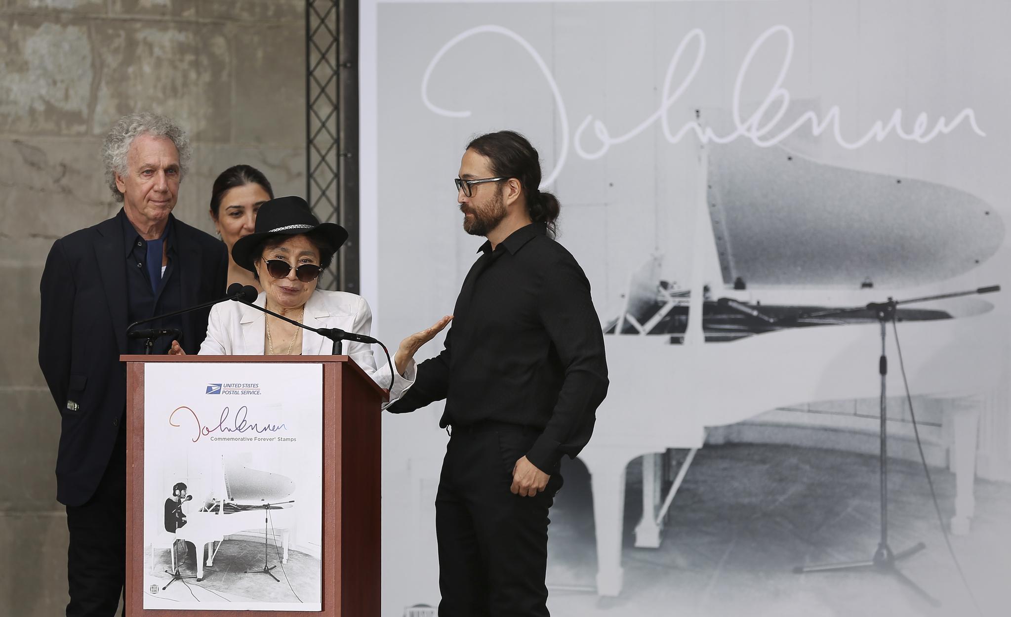 기념식에서 오노 요코가 존 레논에 대한 헌사를 하고 있다. 뒤에 보이는 사진은 우표 뒷면에 실린 존 레논의 흑백 사진. [AP=연합뉴스]