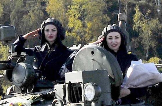 러시아 승무원들이 9일(현지시간) 승무원의 날 기념식에서 꽃다발을 받은 뒤 거수경례를 하고 있다. [타스=연합뉴스]