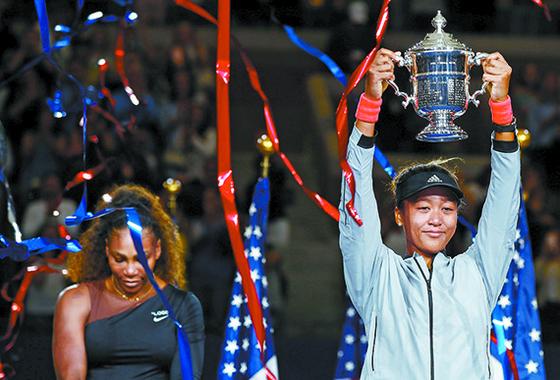 US오픈 테니스 여자 단식 결승전에서 '우상' 세리나 윌리엄스(왼쪽)를 누르고 우승 트로피를 들어 올린 오사카 나오미. 프로 데뷔 5년 만에 처음으로 메이저 대회 결승에 올라 우승을 달성했다. [AFP=연합뉴스]