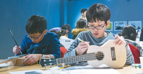 낙원악기상가의 반려악기 만들기 프로그램에 참여한 어린이들이 우쿨렐레를 직접 꾸미고 있다.