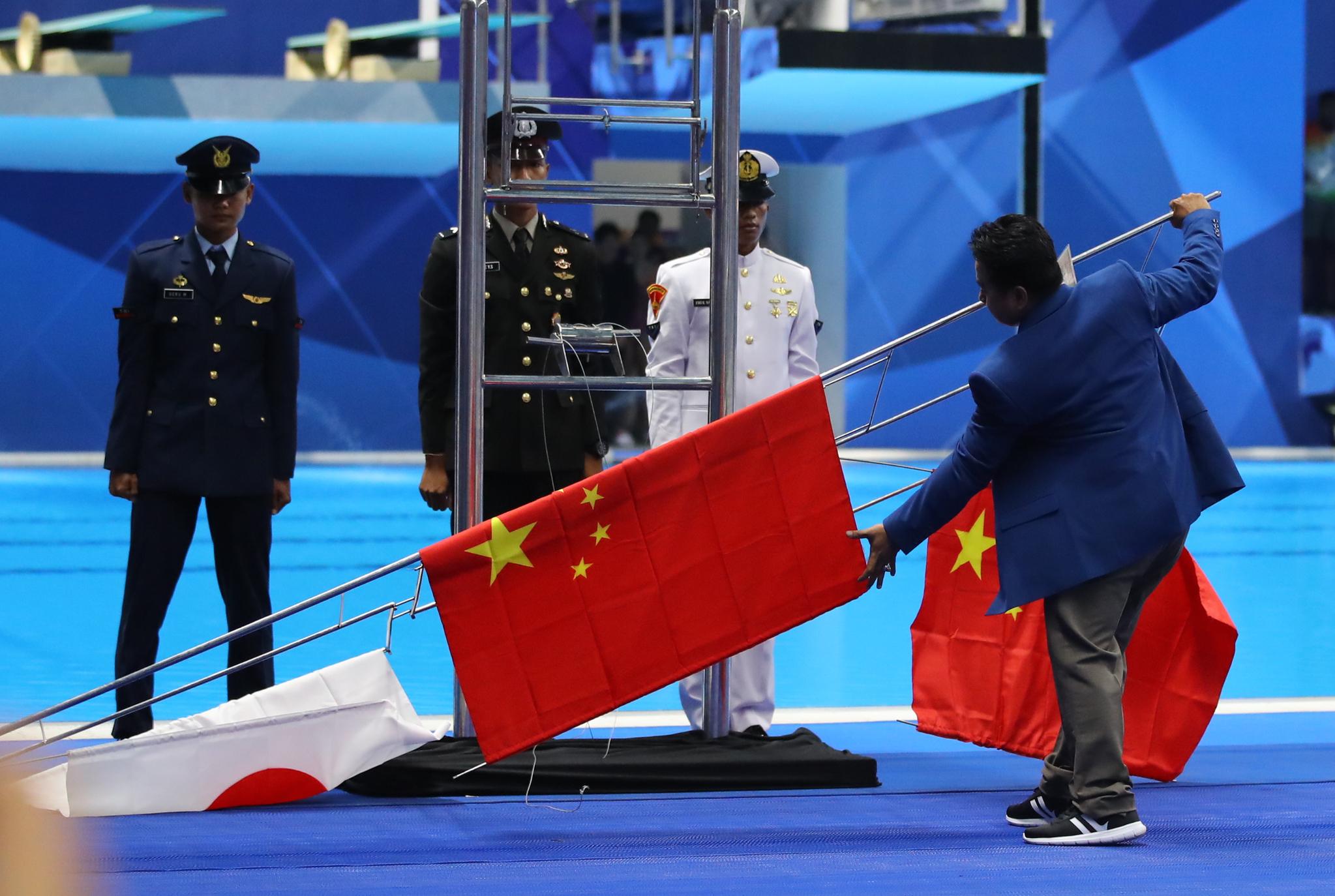 19일 오후 (현지시간) 인도네시아 자카르타 겔로라 붕 카르노 아쿠아틱스타디움에서 열린 2018 자카르타-팔렘방 아시안게임 수영 남자 200m 시상식에서 국가가 울려퍼지자 올라가던 중국과 일본의 국기가 갑자기 바닥에 떨어지자 운영요원들이 수습하고 있다.