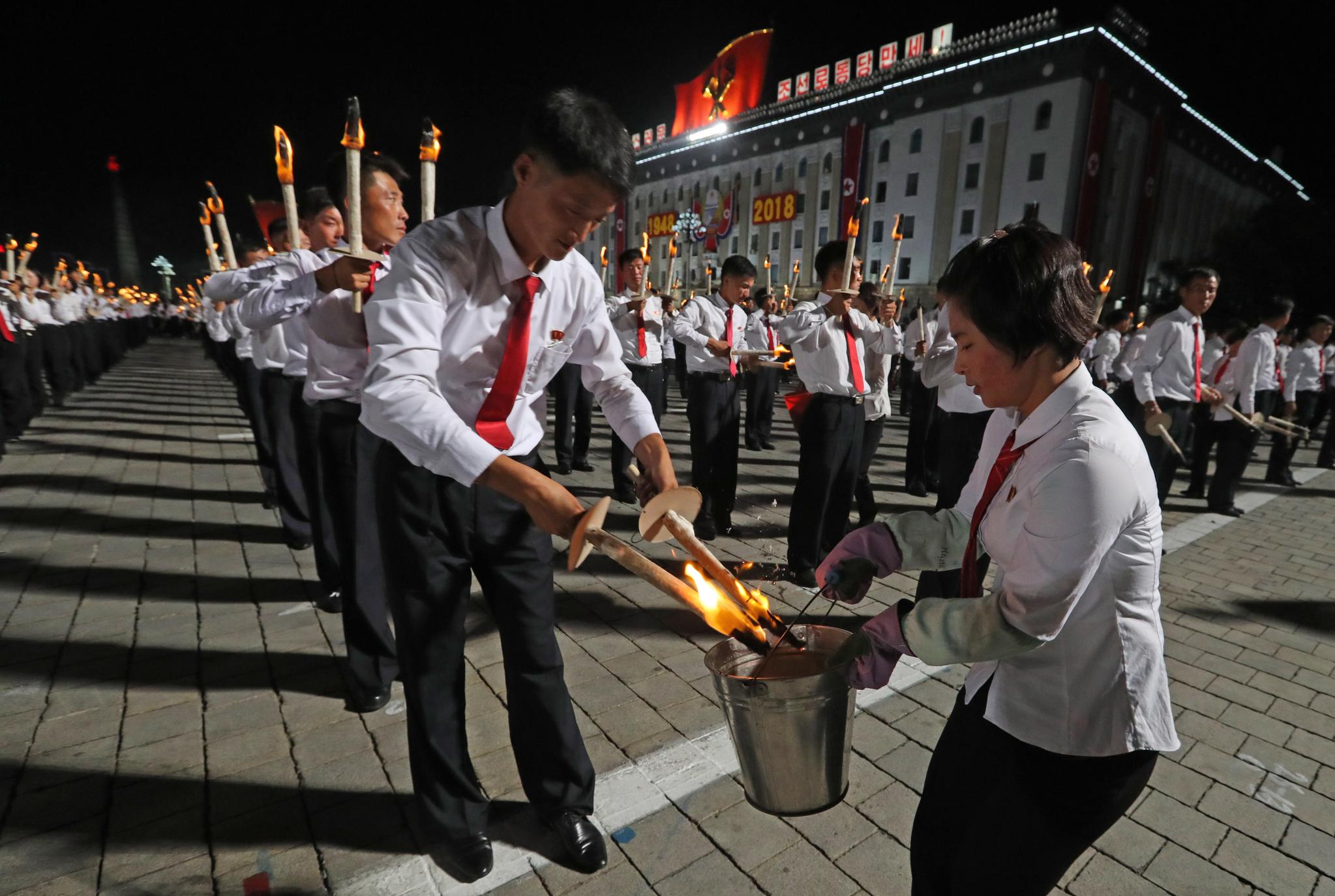 날이 어두워지자 북한 청년들이 횃불에 불을 붙이고 있다. [타스=연합뉴스]
