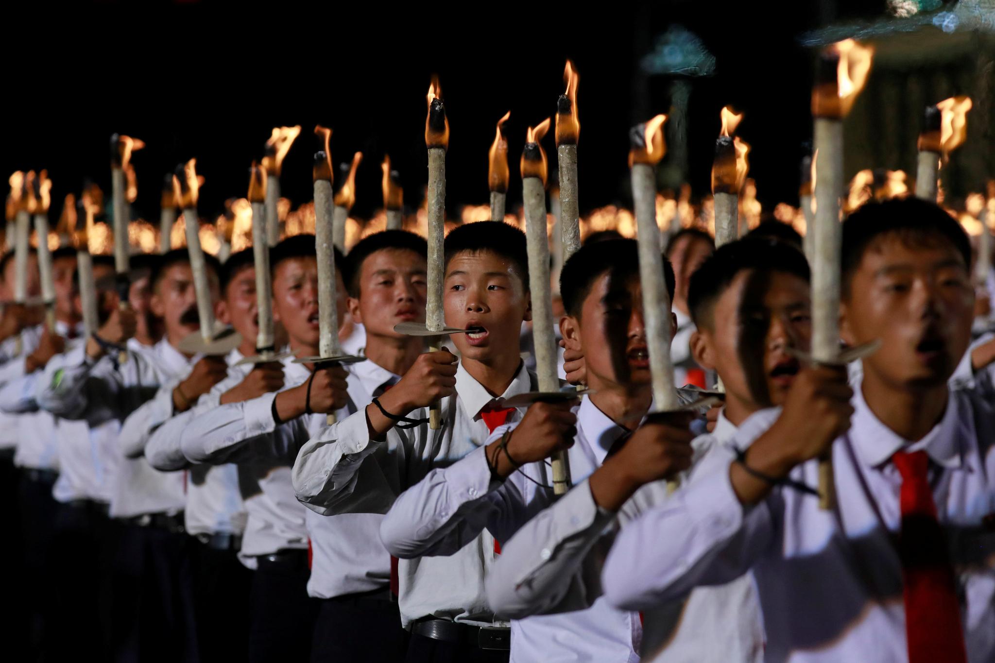 북한 학생들이 함성을 지르며 행진하고 있다. [로이터=연합뉴스]