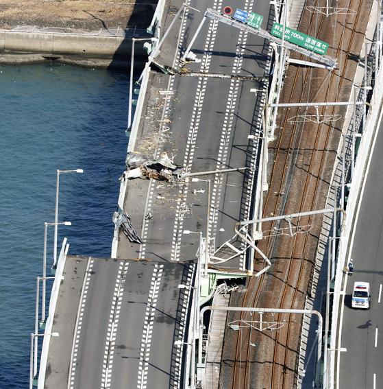 전날 강풍에 휩쓸린 유조선이 충돌했던 간사이 공항 연결다리의 5일 모습. 간사이 공항과 육지를 잇는 연결다리의 왼쪽이 파손돼 있다. 오른쪽 도로를 이용해 공항에 고립됐던 승객들이 육지로 이동했다. 그 사이에 보이는 철로는 아직 정상화되지 않고 있다.[AP=연합뉴스]
