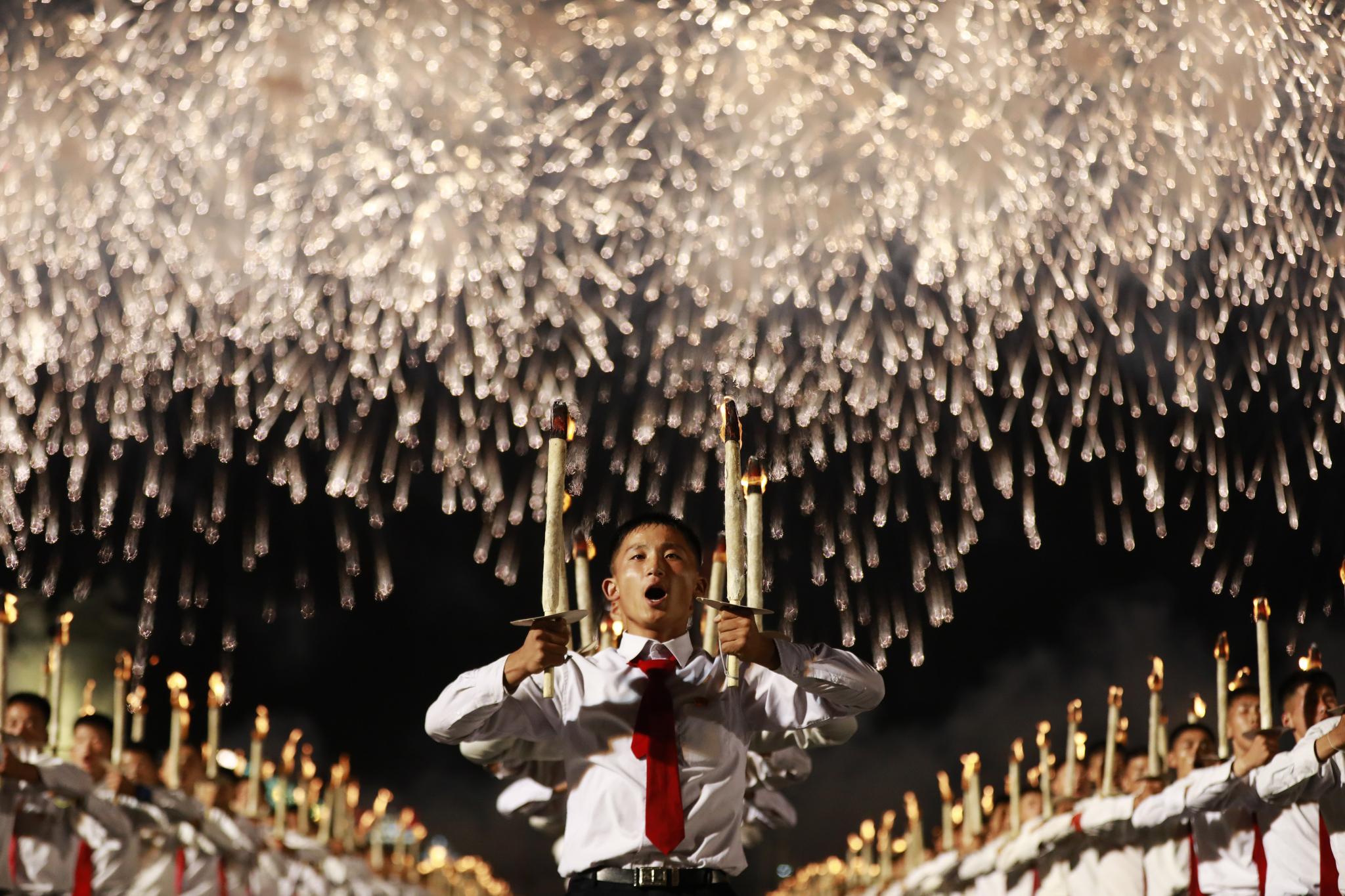 횃불을 든 수천명의 북한 청년들이 머리위로 불꽃이 터지고 있다. [EPA=연합뉴스]