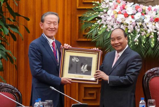 기업인 20여명과 함께 '경제계 미션단' 활동으로 베트남을 찾은 허창수 전경련 회장(왼쪽)이 10일 응우옌 쑤언 푹 총리(오른쪽)를 예방해 기념품을 전달받고 있다. 복을 기원하는 의미의 은실공예 액자다. [사진 전경련]