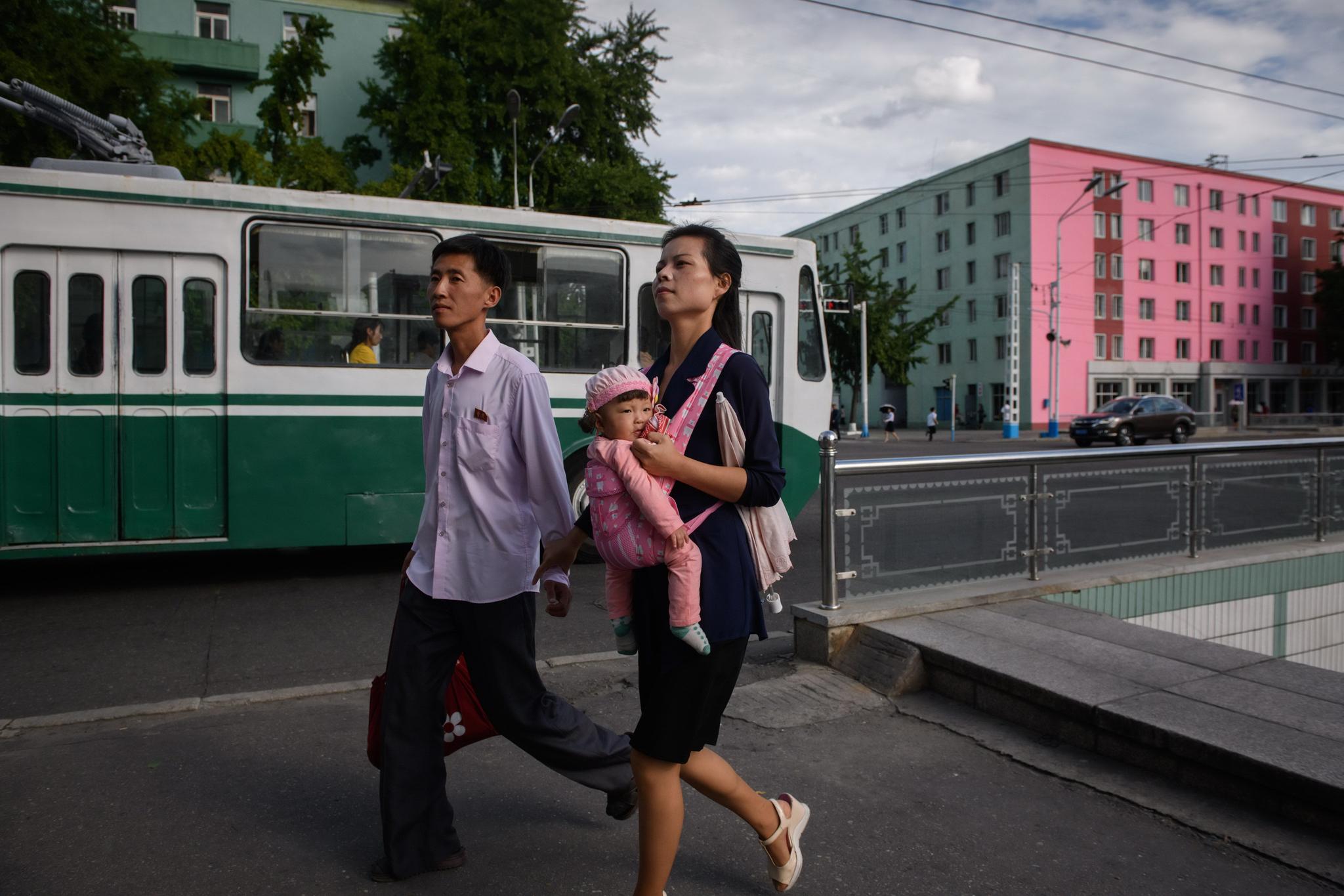 11일 한 북한 남성과 포대기로 아이를 안고 있는 여성이 평양 시내를 걷고 있다. 오른쪽 분홍색 건물과 아이 포대기의 분홍색이 눈에 띈다. [AFP=연합뉴스]