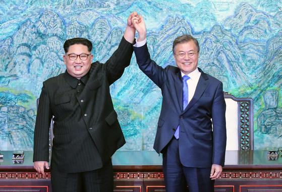 문재인 대통령과 북한 김정은 국무위원장이 4월 27일 오후 판문점에서 '판문점 선언문'에 서명한 뒤 맞잡은 손을 높이 드는 모습. [연합뉴스]
