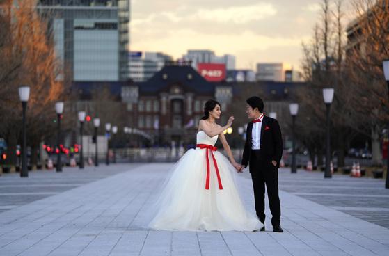 도쿄역 앞에서 웨딩 사진 포즈를 취하고 있는 일본인 예비 신혼 부부. [사진 AP Photo]