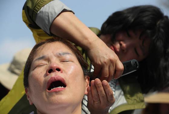 지난 4월 2일 오후 서울 청와대 인근에서 발달장애인 부모가 발달장애인 국가책임제 도입을 촉구하며 삭발을 하고 있다. 연합뉴스