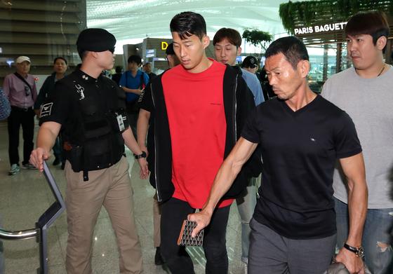 손흥민(가운데)이 아버지 손웅정(오른쪽 두 번째) 씨와 함께 인천국제공항을 통해 출국하고 있다. [뉴스1]