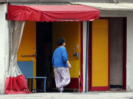 29일 오전 인천의 유일한 집창촌인 인천시 남구 숭의동 '옐로하우스' 내 한 점포 앞을 시민이 지나가고 있다. [연합뉴스]