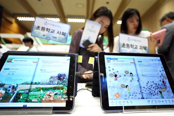 지난 13일 오후 서울 강남구 코엑스에서 열린 2018 이러닝 코리아 국제 박람회를 찾은 관람객이 초등학교 디지털 교과서를 살펴보고 있다. [연합뉴스]