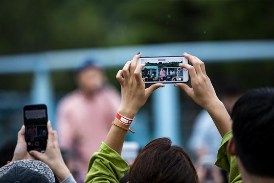 한 참가자가 가수들의 공연을 휴대전화로 촬영하고 있다. 박종근 기자