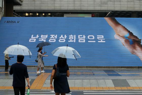 남북정상회담을 이틀 앞둔 16일 서울 세종대로를 지나는 시민들의 모습. 남북정상회담 관련 문구가 계단을 장식하고 있다. 장진영 기자