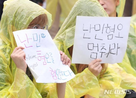 16일 오후 서울 보신각 앞에서 난민인권센터 등 주최로 열린 '난민과 함께하는 행동의 날' 집회에서 참가자들이 '난민 혐오를 멈춰라' 메세지가 적힌 손팻말을 들고 있다. [뉴시스]