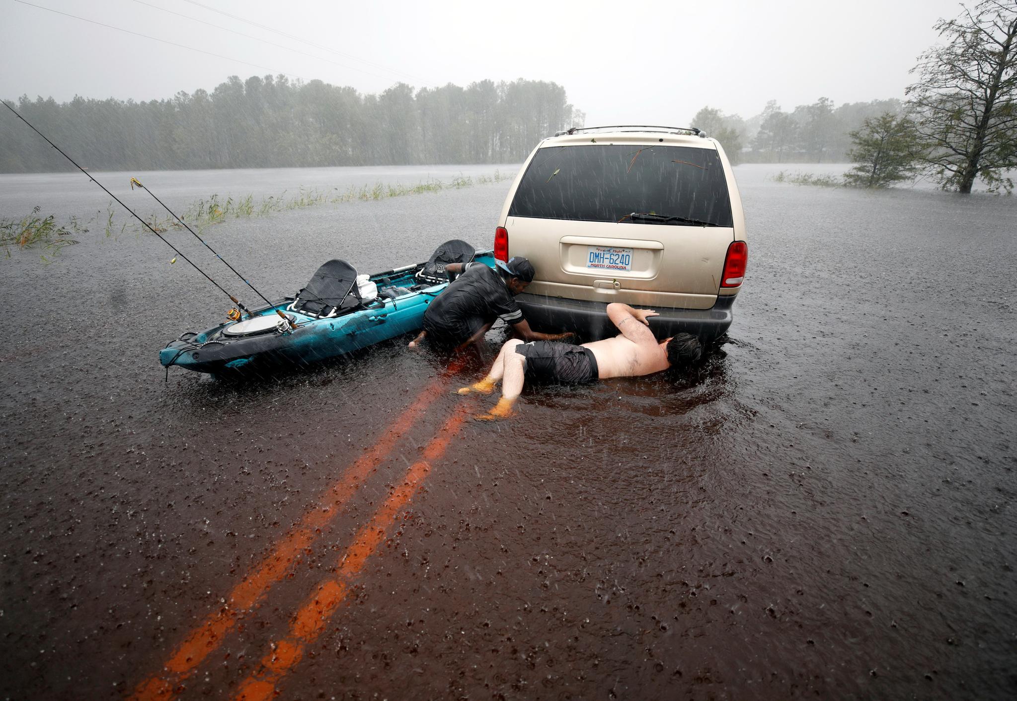 노스캐롤라이나에서 두 청년이 물에 빠진 뒤 견인된 차량의 견인줄을 풀고 있다. [REUTERS=연합뉴스]