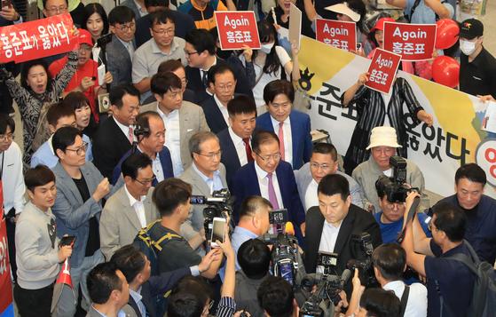 홍준표 전 자유한국당 대표가 두 달간의 미국 생활을 마치고 15일 오후 인천국제공항을 통해 귀국하며 지지자들을 뒤로하고 밖으로 나서고 있다. [연합뉴스]